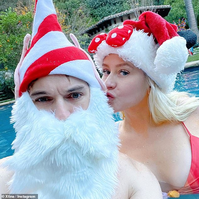 Mrs. Claus: The 40-year-old wore a Minnie Mouse Santa hat with her swimsuit while she was walking around Rutler, 25, in the pool, and wrote: