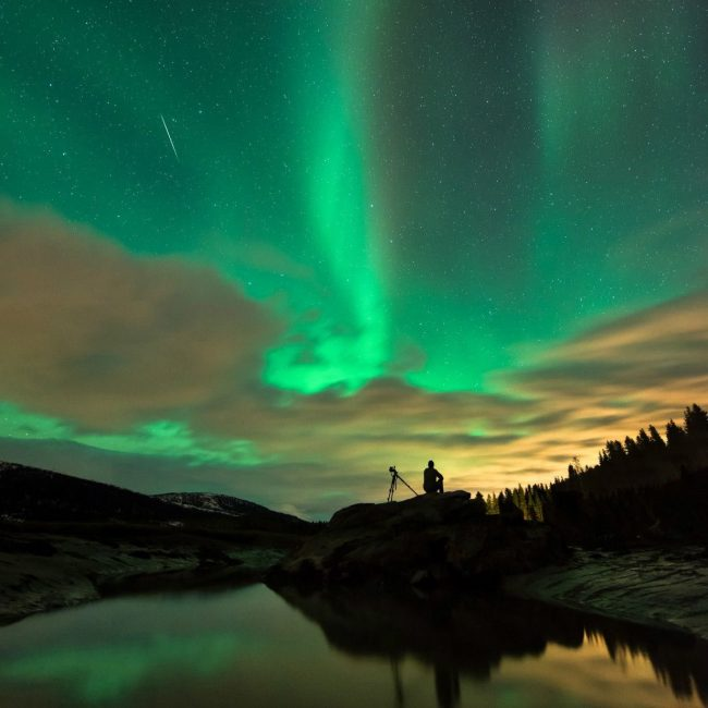 A man with a camera tripod shadowed watching a thin line in the sky against a giant green aurora.